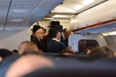 在飞行期间,正统犹太人在飞机祈祷 库存照片