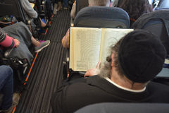 在飞行期间,正统犹太人在飞机祈祷 免版税库存图片