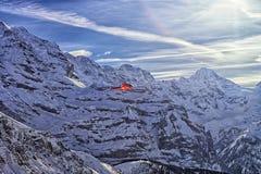 在飞行瑞士的阿尔卑斯的红色直升机高 免版税图库摄影