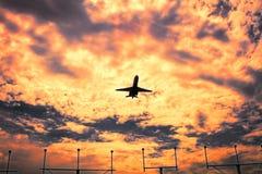 在飞行的喷气式飞机航空器在日落,剧烈的天空 免版税图库摄影