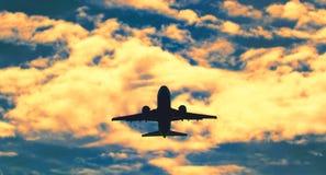 在飞行的喷气式飞机航空器在日落,剧烈的天空 库存图片