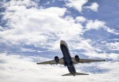 在飞行的喷气式飞机航空器,多云天空 免版税库存图片