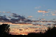 在飞行的多彩多姿的多云日落 免版税库存照片