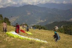 在飞行的山坡火车的滑翔伞反对一绿色山谷和云彩的背景 免版税库存图片