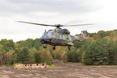 在飞行的德国军用直升机在战场 免版税图库摄影