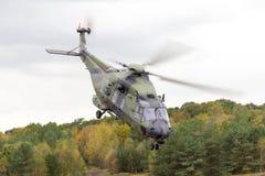 在飞行的德国军用直升机在战场 免版税库存照片