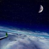 在飞行的飞机翼在云彩和月亮 免版税库存照片
