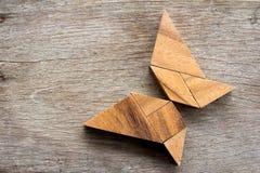在飞行蝴蝶形状的木七巧板难题 免版税库存照片
