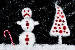 在飞雪期间的不快乐的雪人和xmas树 免版税库存照片