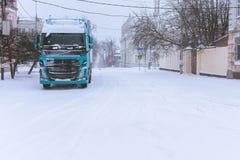 在飞雪的一个城市停放的卡车 免版税库存图片