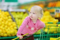 在食品店的逗人喜爱的一点小孩女孩购物 免版税库存图片