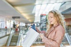 在食品杂货袋惊奇的妇女看起来 免版税库存图片