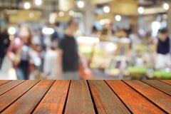 在食物中心的被弄脏的图象木桌在商城和peo 免版税库存照片
