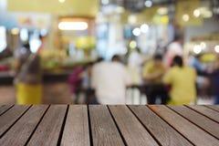 在食物中心的被弄脏的图象木桌在商城和peo 免版税库存图片