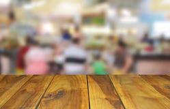 在食物中心的被弄脏的图象木桌在商城和peo 免版税图库摄影