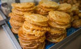 在食物市场上的一块板材堆的甜zlabia 免版税库存照片