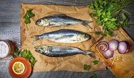 在食物纸、荷兰芹、大海盐和一个杯子的三条鱼鲱鱼在一张木桌上的泡沫啤酒 顶视图 库存照片