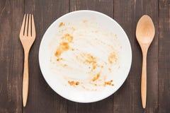 在食物以后的空的盘在木背景 免版税库存照片