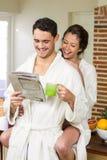 在食用茶和读报纸的浴巾的年轻夫妇 免版税库存照片