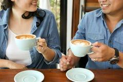在食用蓝色牛仔裤的衬衣的微笑的asain夫妇热的心脏拿铁艺术咖啡 库存照片