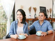 在食用蓝色牛仔裤的衬衣的愉快的asain夫妇热的心脏形状拿铁艺术咖啡一起 免版税库存照片