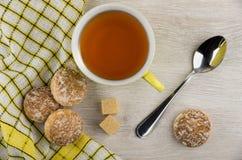 在餐巾、多块的糖、茶匙和茶的蜂蜜蛋糕 库存图片