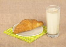 在餐巾和玻璃牛奶的新鲜的新月形面包 免版税库存图片