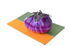 在餐巾的圆的茄子 库存图片