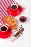 在餐巾,咖啡的新近地被烘烤的新月形面包在红色杯子的在白色木背景 法国断裂的早餐新鲜的酥皮点心 库存照片