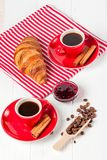在餐巾,咖啡的新近地被烘烤的新月形面包在红色杯子的在白色木背景 法国断裂的早餐新鲜的酥皮点心 免版税图库摄影