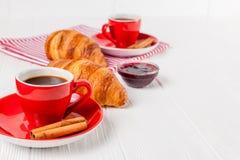 在餐巾,咖啡的新近地被烘烤的新月形面包在红色杯子的在白色木背景 法国断裂的早餐新鲜的酥皮点心 免版税库存照片
