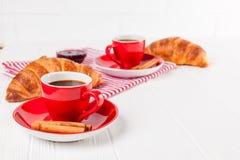 在餐巾,咖啡的新近地被烘烤的新月形面包在红色杯子的在白色木背景 法国断裂的早餐新鲜的酥皮点心 图库摄影