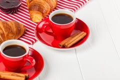 在餐巾,咖啡的新近地被烘烤的新月形面包在红色杯子的在白色木背景 法国断裂的早餐新鲜的酥皮点心 免版税库存图片
