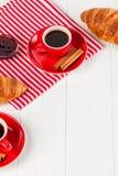 在餐巾,咖啡的新近地被烘烤的新月形面包在红色杯子的在白色木背景 法国断裂的早餐新鲜的酥皮点心 库存图片