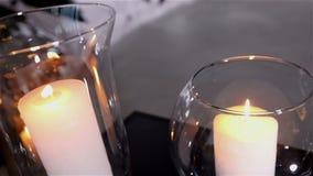 在餐桌、玻璃和圣诞节蜡烛在桌上,白色蜡candleswith玻璃上的装饰蜡烛 股票录像