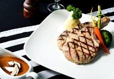 在餐桌上的烤Porkchop牛排 免版税图库摄影