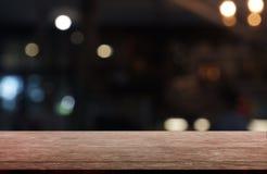 在餐馆、咖啡馆和咖啡馆内部前面抽象被弄脏的背景的空的黑暗的木桌  能使用为 免版税库存照片