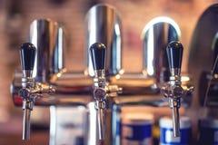 在餐馆、酒吧或者客栈的啤酒轻拍 啤酒草稿特写镜头细节连续轻拍 免版税图库摄影