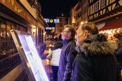 读在餐馆前面的人们圣诞节菜单 免版税库存照片