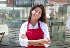 在餐馆前面的笑的白种人女服务员 免版税库存图片