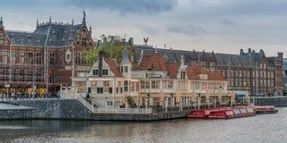 在餐馆前面的运河船在中央驻地前面在Amstedam 库存图片