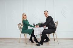 在餐馆喜爱在桌夫妇男人和妇女有葡萄酒杯的坐白色背景 华伦泰晚餐 免版税库存照片
