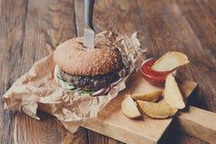在餐馆服务的桌上的快餐 汉堡和土豆楔子 免版税库存照片