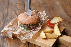 在餐馆木桌上的快餐 汉堡和土豆楔子 免版税库存图片