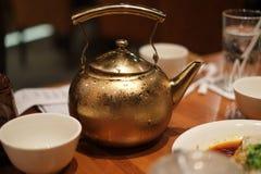 在餐馆桌上的古老经典茶壶 免版税库存照片