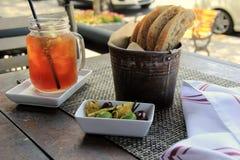 在餐馆的室外餐桌,用被冰的茶,充塞了橄榄和新鲜面包在placemat 免版税库存照片