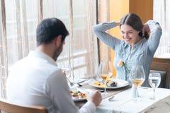 在餐馆的微笑的夫妇吃主菜 库存照片