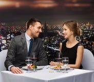 在餐馆的微笑的夫妇吃主菜 免版税库存图片