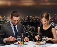 在餐馆的微笑的夫妇吃主菜 图库摄影