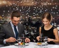 在餐馆的微笑的夫妇吃主菜 库存图片